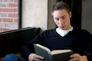 A young male college student reads a book at the library.