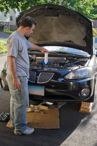A young man adding oil to his car at the end of an oil change.