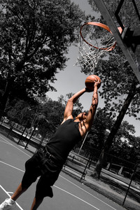 A young man driving to the basketball hoop for a dunk with selective color.