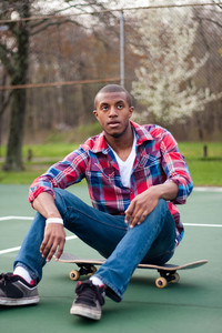 A young man hanging out in the tennis courts sitting on his skateboard.