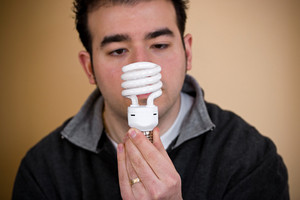 A young man holding an energy saving compact fluorescent light bulb.  Shallow depth of field with stronger focus on the bulb.