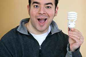 A young man holding an energy saving compact fluorescent light bulb.