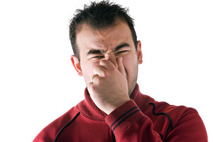 A young man holds or pinches his nose shut because of a stinky smell or odor.