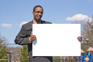A young man holds up a blank white sign with copyspace.