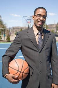 A young man in a business suit at the empty outdoor basketball court.