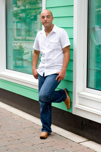 A young man in a casual pose in the city.