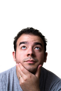 A young man in his middle 20s with his hand on his chin looks like he is thinking deeply about something.