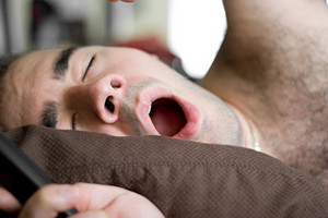 A young man is stretching and yawning in bed.