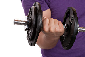A young man lifting a dumbbell isolated over a white background.