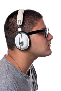 A young man listens to music with a set of head phones over a white background.