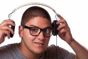 A young man listens to music with a set of head phones.
