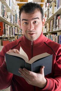 A young man looking at a book in the aisles of shelves at the library.  Shallow depth of field with focus on the face.