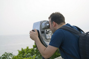 A young man looks through some coin-operated binoculars at the sea shore.