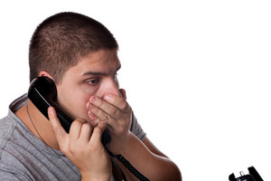 A young man on the phone places his hand on his mouth in disbelief of the news he has just heard.