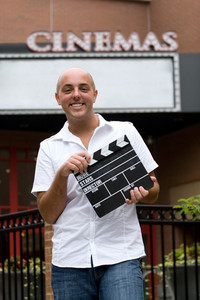 A young man or movie critic holding a movie directors clap board in front of the cinemas.
