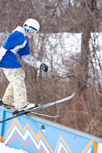 A young man performs a rail slide on skis.