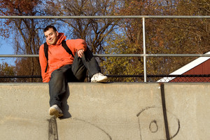 A young man posing at the top of a skateboard ramp.