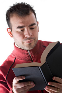 A young man reading a book with a serious expression on his face.