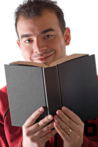 A young man reading a book with a smile on his face.