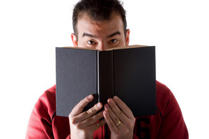 A young man reading a book with a surprised expression on his face.