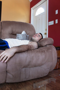 A young man sick on the couch with the tissue box on his chest.