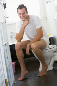A young man sitting in the bathroom