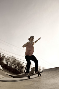 A young man skateboarding down a ramp at the skate park in sepia tone.