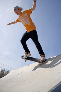 A young man skateboarding down a ramp at the skate park.
