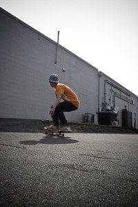 A young man skateboarding in an urban area.