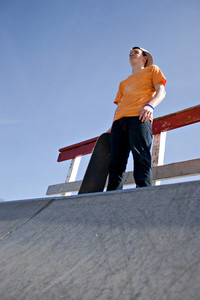 A young man skateboarding standing at the top of a ramp at the skate park prior to attempting a trick.