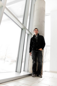 A young man standing by some large windows from a low angle perspective.
