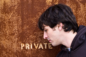 A young man standing outside an old door or entrance that reads PRIVATE.  A great image for any identity theft concept.