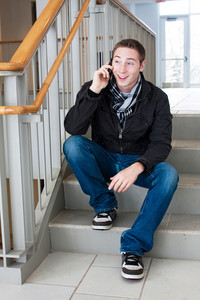 A young man stops to sit on the stairs and talk on his cell phone.