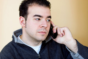 A young man talking on his cell phone.  He is holding the phone with his right hand but listening with his left ear.