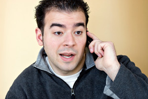 A young man talking on his cell phone with a concerned look on his face.
