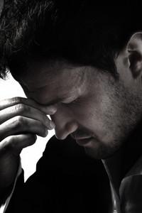 A young man that has an intense headache.