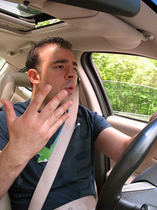 A young man that is driving seems to be experiencing some minor road rage.