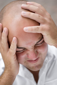 A young man that looks to be upset and grabbing his head in pain or anguish.