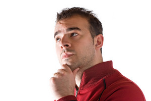 A young man thinking about something deeply with his hand on his chin.