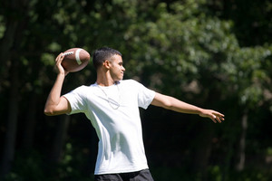 A young man throwing a football outdoors.