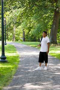 A young man walking on campus with his backpack and a positive attitude.