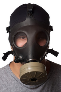A young man wears a gas mask isolated over a white background.