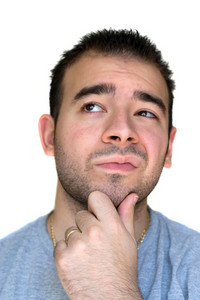 A young man with his hand on his chin thinking an important decision - isolated over white.