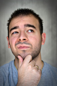 A young man with his hand on his chin thinking an important decision.