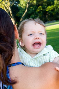 A young mother holding her screaming and crying baby son.