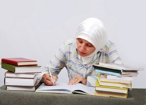 A young muslim woman in traditional clothes in education process