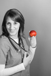 A young nurse is holding up an apple.  An apple a day keeps the doctor away.