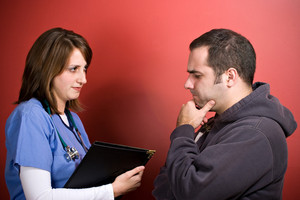 A young nurse talks to a patient during his visit. The man looks concerned about his health.