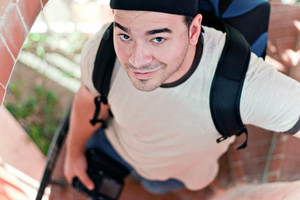 A young photographer in his late twenties with his camera backpack and dslr in hand walking down a spiral staircase. Shallow depth of field.