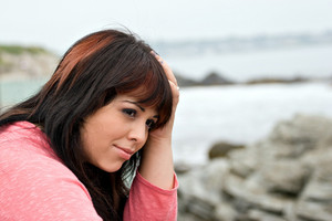 A young plus size model looking depressed or thinking deeply about something by the sea shore.